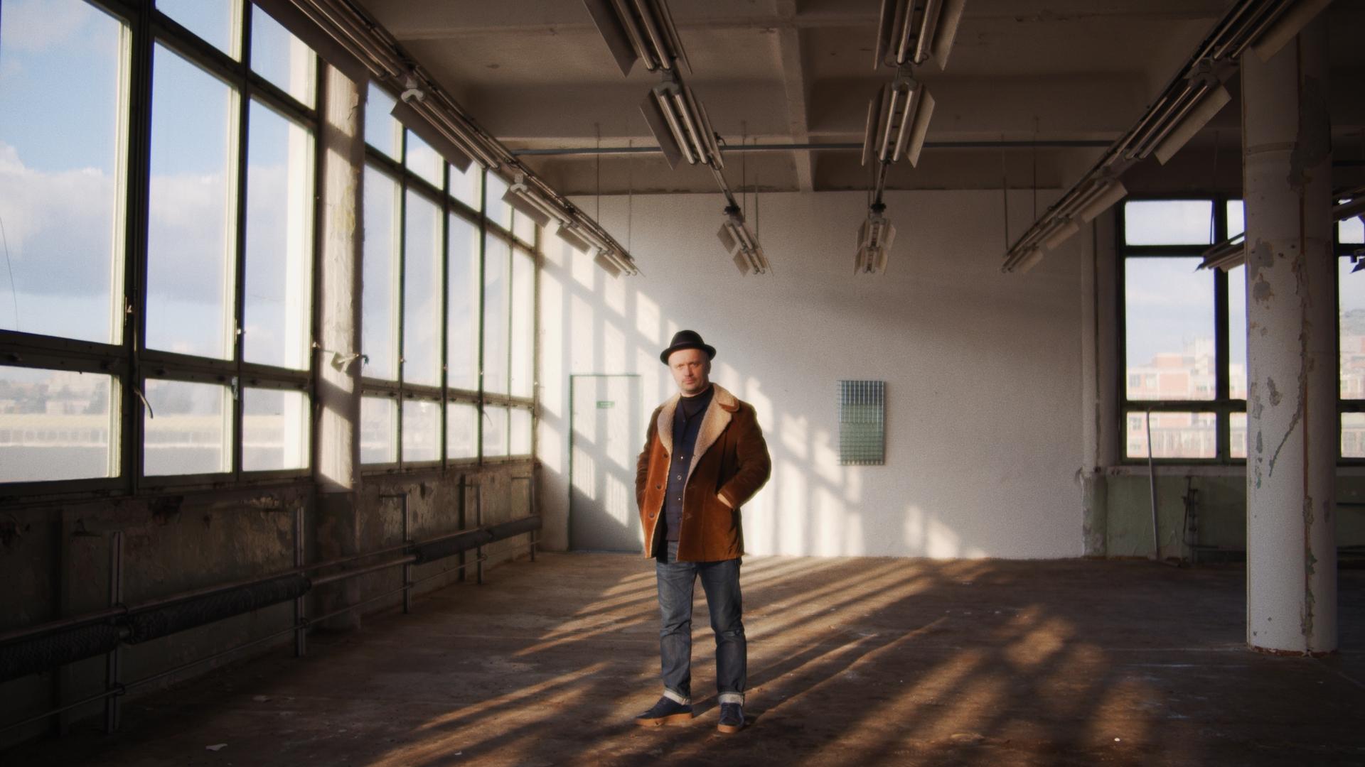 Portrét Petra Stanického, postava muže v prázdné továrně.